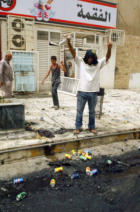 An Iraqi man reacts at the site where a car bomb exploded in Baghdad's Karrada area, 01 August 2007. The explosion ripped through a main intersection in a busy Baghdad shopping district, killing at least 10 Iraqis and wounding another two dozen, medics sa