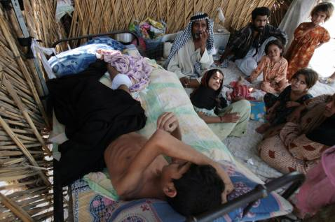 An internally displaced Iraqi family sit with a wounded relative (L) lying on a bed in their mud and reed hut erected on unoccupied land in the central Al-Karrada neighbourhood of Baghdad, August 2007.