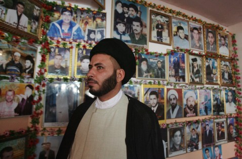 Iraqi chief of Sadr City social committee Faraid al-Mussawi poses in front of pictures showing Martyrs killed during the fights between US and Iraqi security forces against Shiite Muslim militiamen in 2004.