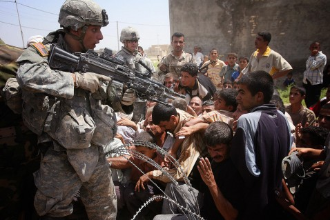 An US soldier gestures with his M249 SAW (Squad Automatic Weapon) as Iraqis rush to receive humanitarian aid from the Iraqi Ministry of Trade in Mufrek, western Baquba, 60 kms (35 miles) north of Baghdad, 05 August 2007.