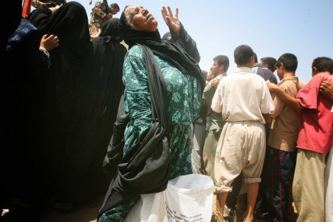 An Iraqi woman rests after rushing through a crowd to receive humanitarian aid from the Iraqi Ministry of Trade in Baquba, 60 kms (35 miles) north of Baghdad, 05 August 2007.