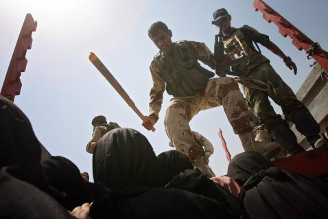 Iraqis soldiers try to push back Iraqi woman as they rush to receive humanitarian aid from the Iraqi Ministry of Trade in Baquba, 60 kms (35 miles) north of Baghdad, 05 August 2007.