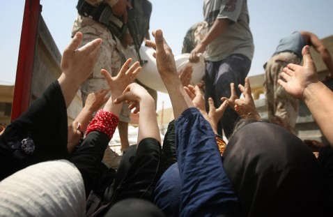 Iraqi women raise their hands to receive humanitarian aid from the Iraqi Ministry of Trade in Baquba, 60 kms (35 miles) north of Baghdad, 05 August 2007.