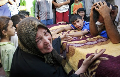 An Iraqi family mourns over the coffin of a relative killed during a US military air strike in the predominantly Shiite Baghdad suburb of Sadr City, 08 August 2007.