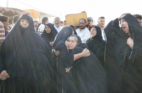 Iraqis women mourn as men carry the coffin of their relatives killed during an US military air strike in the predominantly Shiite Baghdad suburb of Sadr City, 08 August 2007.