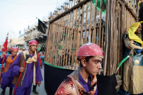 Iraqi Shiites dressed in costumes parade with a wooden cage representing the prison in which the revered Imam Musa Kadhim was poisoned in the year 799, during a major religious festival, 08 August 2007 at the Kadhimiyah district of Baghdad.