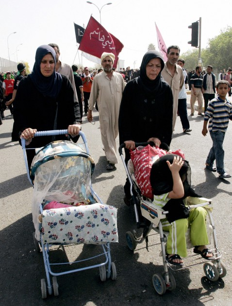 Iraqi Shiite women push their children in trollies as they walk with others worshippers towards the Kadhimiyah district of Baghdad to pay homage to the revered Imam Musa Kadhim at his shrine, 09 August 2007.