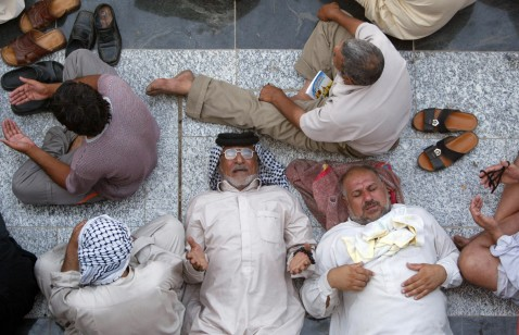Iraqi Shiite worshippers rest whilst others pray as they pay homage at the shrine of the revered Imam Musa Kadhim in the Kadhimiyah district of Baghdad, 09 August 2007.