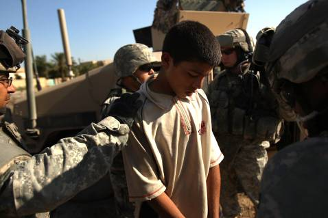 BAGHDAD, IRAQ - AUGUST 16: Troops from U.S. Army Delta Company 212 Cavalry detain a boy suspected of planting an IED (Improvised Explosive Device) in the Ghazaliya neighborhood, which has been used as a base by Sunni insurgents, August 16, 2007 in Baghdad.