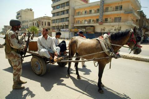 An Iraqi soldier talks with the driver of a horse-pulled cart at a checkpoint in central Baghdad, 17 August 2007.