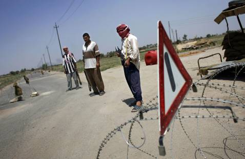 Iraqi Sunni volunteers, former insurgents who have joined forces with US and Iraqi troops to fight Al-Qaeda, stand guard at a makeshift checkpoint in southern Baghdad 19 August 2007.