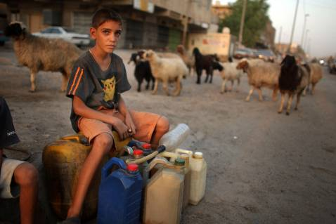 BAGHDAD, IRAQ - AUGUST 27: A boy sells gasoline to morning customers on a street corner August 27, 2007 in the Hurriya neighborhood in Baghdad, Iraq.