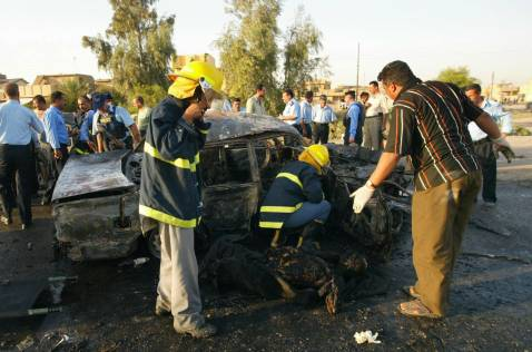 The remains of a burnt body lies on the ground after Iraqi rescue workers removed it from a vehicle that burnt as a result of a car bomb in Kirkuk, north of Baghdad, 29 August 2007. Four people died in the explosion and eight were wounded.