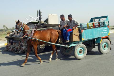 Iraqis ride a horse-drawn cart past soldiers sitting at a checkpoint near Sadr City, east of Baghdad, 30 August 2007.