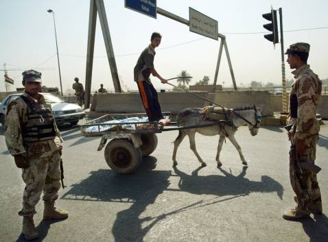 An Iraqi boy rides his horse-drawn cart past Iraqi soldiers manning a checkpoint near Sadr City, east of Baghdad, 30 August 2007.