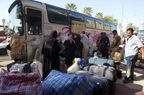 Iraqis put their luggage on a bus leaving for Syria at the al-Salihiya bus station in Baghdad, 05 September 2007.