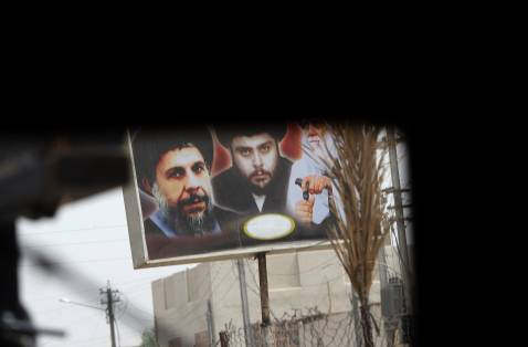 Leaving Muqtada behind? Photo shows billboard of Muqtada al-Sadr, his father, and father in law, all Shi'a clerics venerated by the Sadrist current, through the rear windshield of a US patrol in Baghdad.