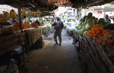 BAGHDAD, IRAQ - SEPTEMBER 12: U.S. Army soldiers patrol through an outdoor market September 12, 2007 in the Hurriyah neighborhood of Baghdad. US Commanders have said that the insurgency generates revenue from mafia-style rackets, even sometimes charging locals taxes on produce and other products.
