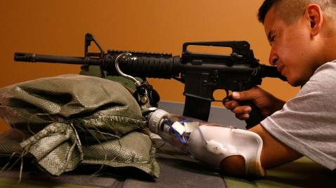 WASHINGTON - SEPTEMBER 12: Army Ssg. Ramon Padilla of 2nd 503rd Airborne Infantry Battle Company, aims an M4 rifle at a firearm training simulator with his prosthetic arm at the newly completed Military Advanced Training Center at Walter Reed Army Medical Center.