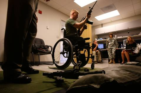 WASHINGTON-SEPTEMBER 12: Marine 1st Lt. Andrew Kinard of 2nd Light Armored Reconnaissance Battalion, injured in October, 2006 in Al-Anbar, holds an M4 rifle at a firearm training simulator of the newly completed Military Advanced Training Center at Walter Reed.