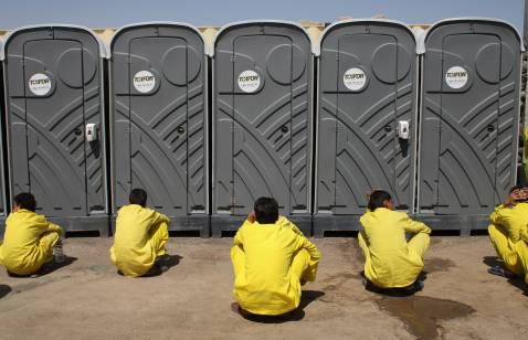 BAGHDAD, IRAQ - SEPTEMBER 19: Juvenile detainees wait for their turn outsideportable bathrooms at the 'House of Wisdom' school operated by the U.S. military near the Camp Cropper detention center September 19, 2007 in Baghdad Iraq.