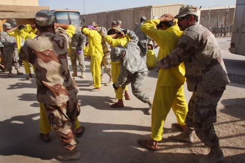 BAGHDAD, IRAQ - SEPTEMBER 20: Iraqi juvenile detainees are bodysearched by U.S. Army guards at the Camp Cropper detention facility before boarding busses for a nearby military-run school September 20, 2007 in Baghdad, Iraq.