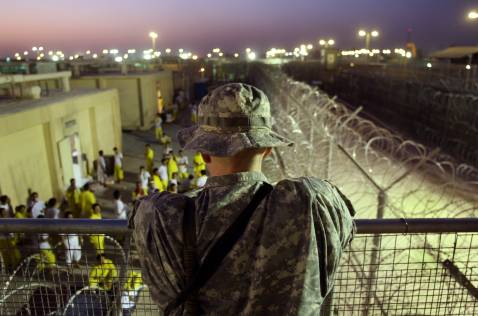 BAGHDAD, IRAQ - SEPTEMBER 19: A U.S. Army soldier watches Iraqi detainees at the Camp Cropper detention center September 19, 2007 in Baghdad, Iraq.