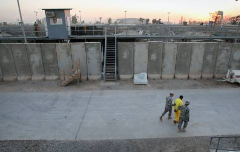 BAGHDAD, IRAQ - SEPTEMBER 20: An Iraqi detainee is escorted by U.S. Army guards past blast walls at the Camp Cropper detention facility September 20, 2007 in Baghdad, Iraq.