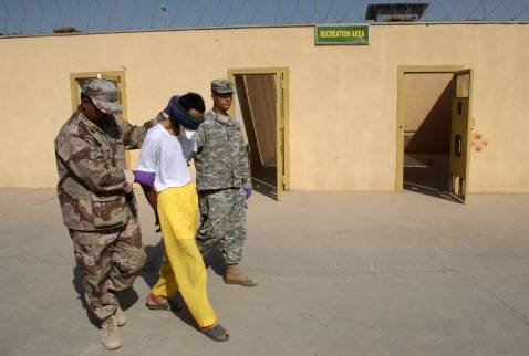 BAGHDAD, IRAQ - SEPTEMBER 20: An Iraqi and an American soldier lead a detainee with Tuberculosis back to his quarrantine cell after his two hours of recreation time at the Camp Cropper detention center September 20, 2007 in Baghdad, Iraq.