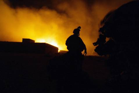 US soldiers equipped with night-vision goggles wait for an airlift next to a burning al-Qaeda hideout, near Iskandaria, south of Baghdad early 21 September 2007.