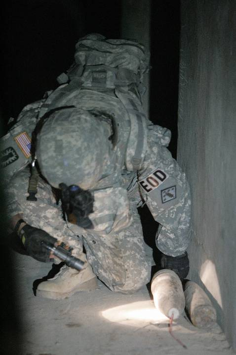A US army explosives expert checks an Improvised Explosive Device (IED) found during a raid in an al-Qaeda hideout near Iskandaria south of Baghdad early 21 September 2007.
