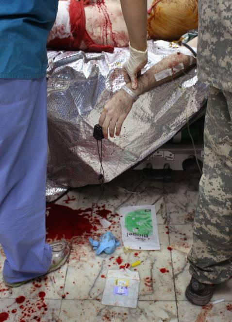 BAGHDAD, IRAQ - SEPTEMBER 22: (EDITOR'S NOTE: GRAPHIC CONTENT) A U.S. Army nurse takes the fading pulse of a dying American soldier at the 28th Combat Support Hospital September 22, 2007 in Baghdad, Iraq.