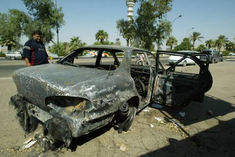 An Iraqi looks 24 September 2007, at a burnt car on the site where Blackwater guards who were escorting US embassy officials opened fire in a shootout which left nine civilians and a policeman dead.