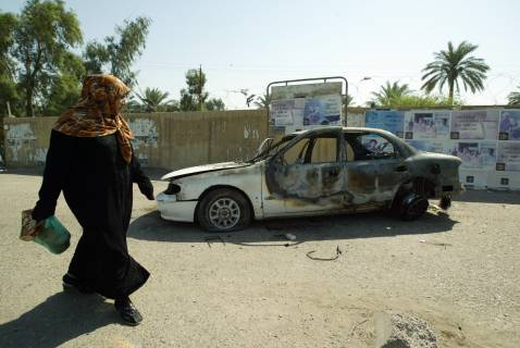 An Iraqi woman walks past a burnt car at Nisoor Square, at the site where Blackwater guards opened fire, killing a number of civilians.
