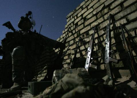 US soldier from Alpha Company of 1/38 Infantry Regiment inspects weapons that were confiscated during an overnight operation outside Baquba, early 26 September 2007, from the US Army registered local protection force the Concerned Local Nationalists (CLN)