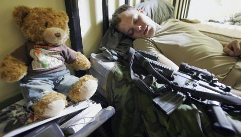 US Army Specialist Luke Weschenfelder, from Billings, MT, of Alpha Company of 1/38 Infantry Regiment sleeps with his M-4 assault rifle next to him, and a teddy-bear, a gift from his girlfriend Brittany, at his company's combat out post outside Baqubah.
