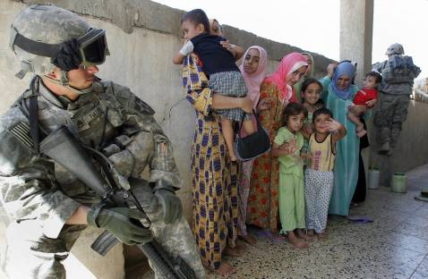US Staff Sergeant Fuller (L) of Alpha Company, 1/38 Infantry Regiment, looks toward Iraqi women and children as he secures an area during a mopping-up operation in Baquba, some 50 kms north-east of Baghdad, 27 September 2007.