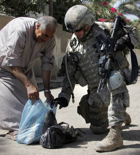 US Army Sergeant of Alpha Company, 1/38 Infantry Regiment, takes a look inside an Iraqi man's bag during a mopping-up operation to search and secure an area, in Baquba, some 50 kms north-east of Baghdad, 27 September 2007.