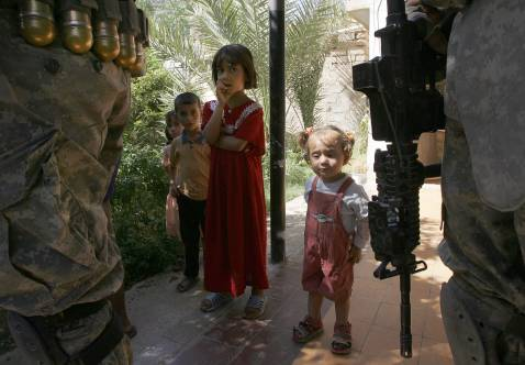 Iraqi children stand watching as US Army soldiers of Alpha Company, 1/38 Infantry Regiment, search their home during a mopping-up operation to search and secure the area, in Baquba, some 50 kms north-east of Baghdad, 27 September 2007.