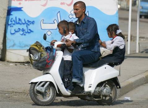 An Iraqi father transports his three children on his motorcycle on the first day of classes, 30 September 2007 in Baghdad.