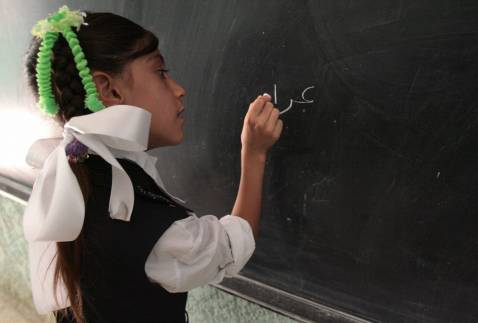 An Iraqi school girl writes the name of her country on the blackboard on the first day of classes, 30 September 2007 in Baghdad.