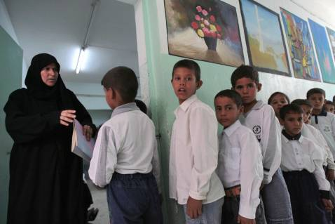 An Iraqi teacher welcomes school boys to the class-room on the first day of classes, 30 September 2007 in Baghdad.
