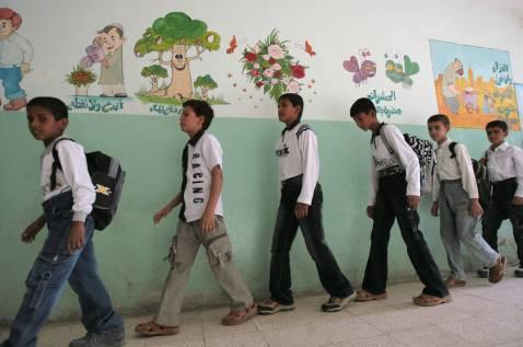 Iraqi teenagers walk towards their class-room on the first day of classes, 30 September 2007 in Baghdad.