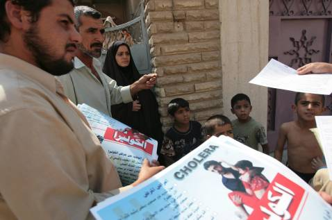 Iraqi members of Moqtada al-Sadr movement help in the Cholera awareness campaign handing out posters to residents of Baghdad's impoverished neighborhood of Sadr City, 30 September 2007.