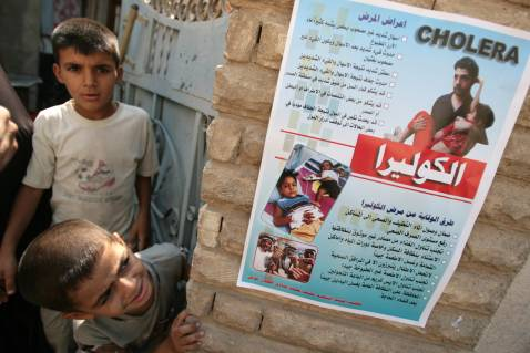 Cholera awareness campaign posters are seen in Baghdad's impoverished neighborhood of Sadr City, 30 September 2007.