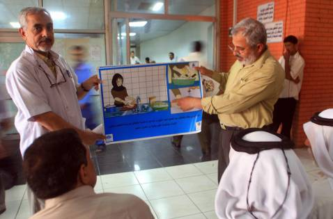 Iraqi health ministry officials display a cholera awareness campaign poster 01 October 2007 in the southern city of Basra.