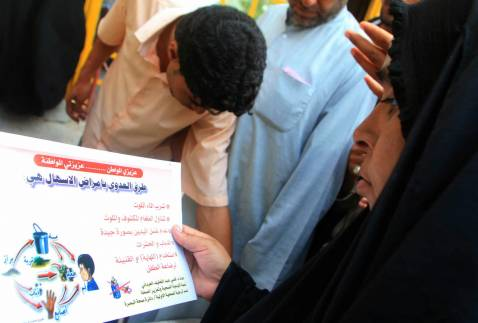 An Iraqi woman reads a Cholera awareness campaign poster Monday in Basra.