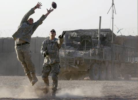 US soldiers from Alpha Company, 1/38 Infantry Regiment, play American football in front of their Stryker Armoured Personnel Carrier (APC) at their combat outpost in Baquba, 02 October 2007.