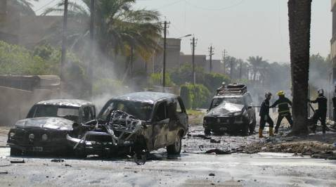 Iraqi firefighters at the site of a triple-bomb attack on the Polish ambassador's convoy in Baghdad on Wednesday. The ambassador was wounded in the attack that killed a civilian and injured three others.