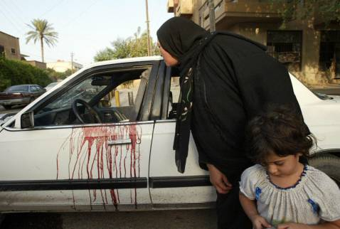 An Iraqi woman peeps inside a blood stained car of two women allegedly shot dead by security guards in a four-car convoy in central Baghdad today.  Officials are trying to determine who fired the shots and why.